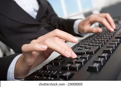Close-up of secretary typing business document on the black keyboard