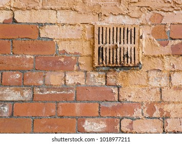 Closeup of section of a brick wall with a rusty iron ventilation cover