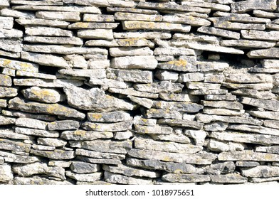 Closeup of section of a dry stone wall with a weathered surface