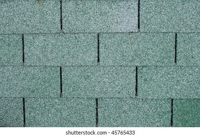 Closeup of a section of green asphalt roofing shingles