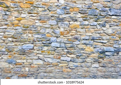 Closeup of section of a stone house wall with a weathered surface