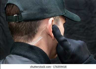 Close-up of a security guard listening to his earpiece. Shot from, over the shoulder.