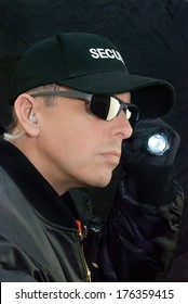 Close-up of a security guard searching with his flashlight.