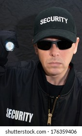 Close-up of a security guard shining a flashlight at the camera.