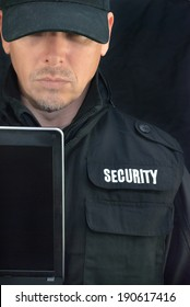 Close-up of security holding a laptop display to camera.