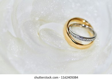 Close-up and selective focus on the diamond head with shallow depth of field of the couple rings, platinum and gold ring on the white fabric background