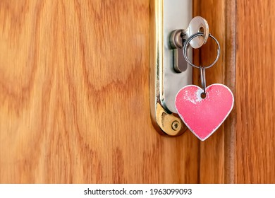 Close-up and selective focus of a red worn metal heart-shaped keychain on the key in the door lock. The concept of an old cheap hotel or motel for the night. Copy space