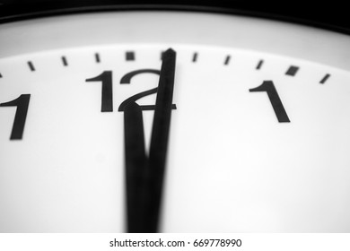 Closeup and selective on the pointers of a clock marking a minute after midnight - black and white rendering. The main focus is on the number twelve and its pointer.