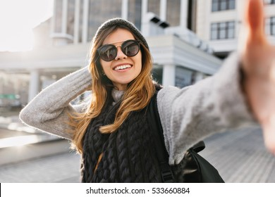 Closeup selfie portrait of joyful fashionable young woman in modern sunglasses, long blonde hair, knitted hat smiling on sunny street in city centre. Cheerful mood, having fun, enjoying sunshine