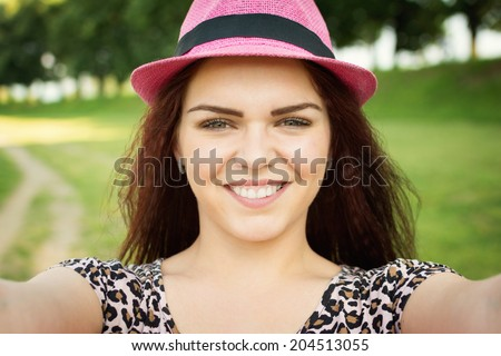 619725bc23 Closeup selfie shot of cute young woman with pink hat and animal print  shirt. Beautiful