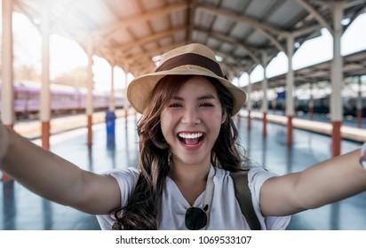 Nahaufnahme des Selbstporträts eines attraktiven Mädchens mit langen Haaren, das am Bahnhof steht. Sie lächelt der Kamera zu und sieht cool aus. Strohhut auf Kopf. Urlaub und Ferien.