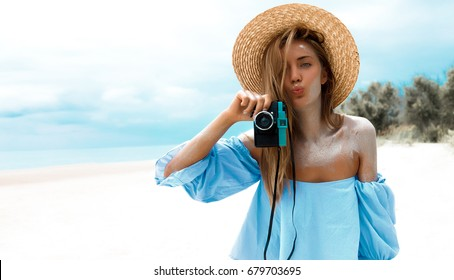 Close-up selfie-portrait of attractive girl with long hair standing over beach,sending kiss. Girl smiling to camera and shows her cool look. Straw hat on head.holiday,vacation.travel picture,vibe