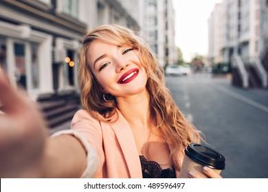 Closeup selfie-portrait pretty blonde girl on street in city. She has vinous lips, smiling to camera