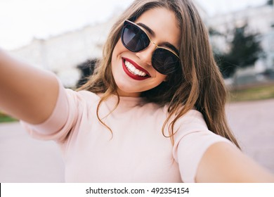 Closeup selfie-portrait student of attractive girl in sunglasses with long hairstyle and snow-white smile in city.