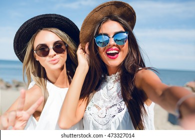 Close-up selfie-portrait of two attractive brunette and blonde girls with long hair standing on the beach. They wear hats, sunglasses and white dresses. They are smiling to the camera.