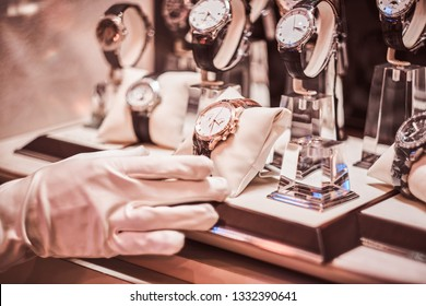 Close-up of the seller's hand in gloves shows the exclusive men's watch from the new collection in the luxury jewelry store