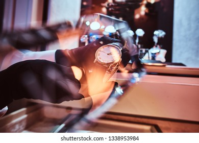 Close-up of the seller's hands in gloves shows the exclusive men's watch from the new collection in the luxury jewelry store