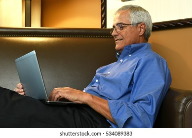 Closeup of a senior businessman sitting on a sofa in his hotel room while using a tablet computer. The man is seen from the side.