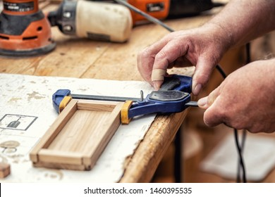 Close-up senior carpenter glueing wooden craft surface and joining with clamps. Woodwork carpenter with equipment and tools at workshop. Handmade diy furniture.Wood part glue joiner