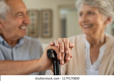 Closeup of senior couple hands holding walking stick. Old husband and wife holding cane handle while looking at each other. Happy retired couple joining hands with love at home.