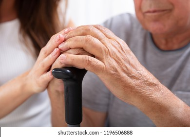 Close-up Of Senior Father And Daughter's Hand On Walking Stick