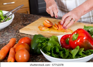 closeup of senior female chopping food ingredients in the kitchen