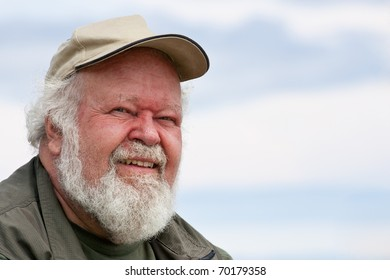 A closeup of a senior male with white beard and hair, in a baseball cap, isolated against sky.