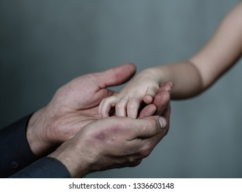 Closeup senior man and baby girl holding hands together on dark background