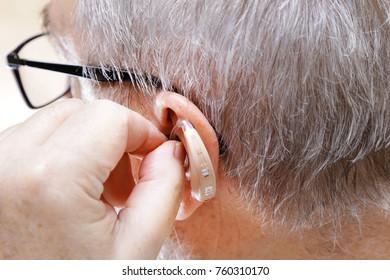 Closeup senior man inserting hearing aid in ear.