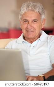 Closeup of senior man with laptop computer at home