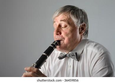 closeup of senior man playing clarinet