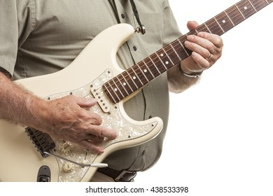 Closeup of senior man playing electric guitar over white background.  Selective focus on hands on fret board neck.