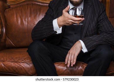 Closeup of senior man sitting at the table having a glass of cognac