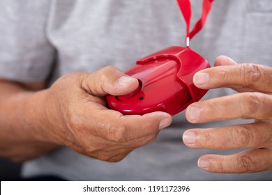 Close-up Of A Senior Man's Hand Holding Red Personal Alarm