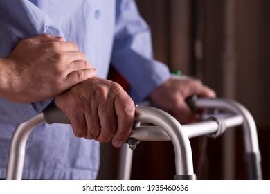Closeup of senior man's hands holding walker at nursing home