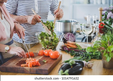 Close-up of senior people cutting tomatoes and mixing salad while preparing healthy dinner