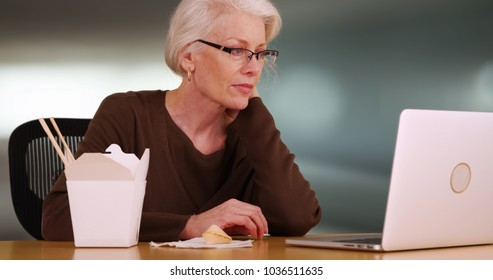 Close-up of senior woman browsing web on laptop while eating Chinese food