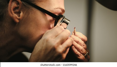 Closeup of senior woman goldsmith checking quality of a diamond. Female jeweler inspecting a gem through magnifying glass in workshop.