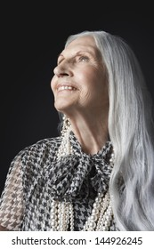 Closeup of a senior woman with long gray hair looking up against black background
