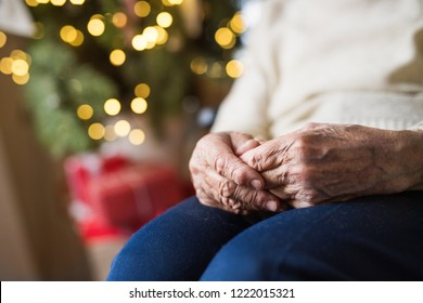 A close-up of a senior woman sitting at home at Christmas time.