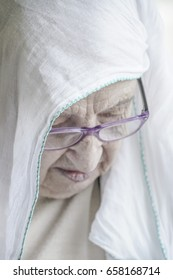 Closeup of a senior woman wearing headscarf while praying