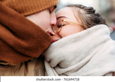 Closeup sensual portrait of young kissing couple in love posing on the street in cold winter portrait, wearing warm scarfs and hats