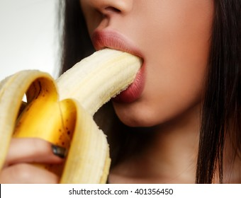 Close-up of sensual woman eating banana isolated on white - oral sex concept