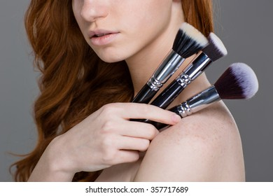 Closeup of sensual young rehead woman with set of makeup brushes over grey background