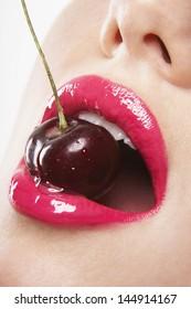 Closeup of sensuous young woman wearing pink lipstick biting cherry