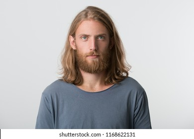 Closeup of serious attractive young man with beard and blonde long hair wears gray t shirt looks pensive and thoughtful isolated over white background