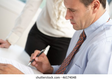 close-up serious boss signing contract with executive secretary near by