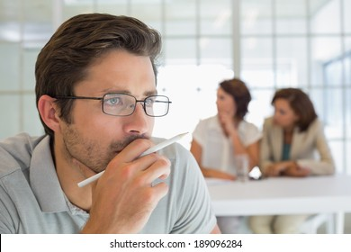 Close-up of a serious businessman with colleagues in meeting in background at the office