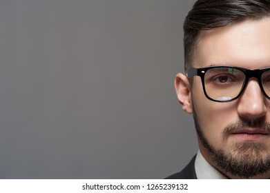 Close-up Serious businessman in formal suit and glasses looks at the camera on gray background. Place for text