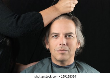 Close-up of a serious man looking to camera while his long hair is shaved off for a cancer fundraiser.